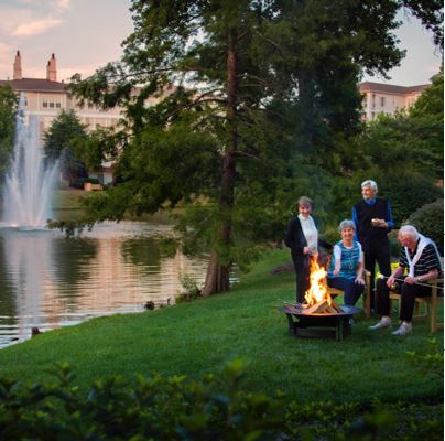 Senior adults enjoying fire and smores by the Cypress lake